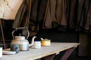 cantina dos trabalhadores antigos com macacão e chaleira na mesa de madeira foto