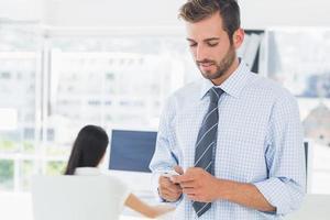 artista masculino casual mensagens de texto com o colega no fundo foto