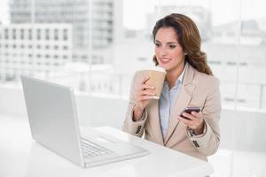 empresária feliz segurando smartphone e copo descartável foto