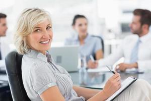 jovem empresária com colegas discutindo no escritório foto