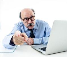 Grito furioso do chefe sênior do homem de negócios 60s e gesticular chateado e louco sentado na mesa na gestão e problemas de estresse no trabalho isolado no fundo branco.
