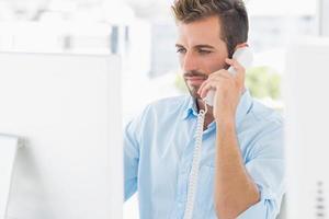 homem sério, usando telefone e computador no escritório foto
