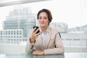empresária sorrindo para seu smartphone foto