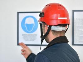 jovem trabalhador manual usando capacete de segurança foto