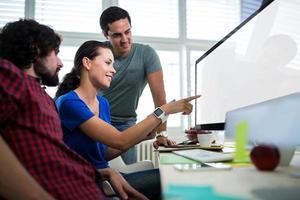 equipe de designers gráficos discutindo sobre o computador foto