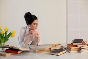 garota de negócios senta-se na secretária de pastas de papel de escritório foto