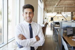 jovem arquiteto masculino latino-americano no escritório, sorrindo para a câmera foto