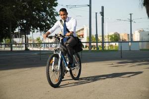 empregado de escritório latino jovem andando de bicicleta para trabalhar foto