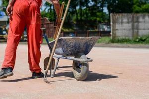 trabalhador da construção civil em calças vermelhas com carrinho de argamassa azul foto