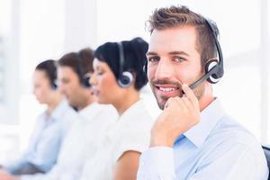 colegas de trabalho com fones de ouvido em uma linha foto