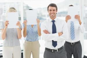 empresário com colegas segurando papel em branco na frente de rostos
