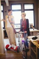 designer gráfico, segurando a bicicleta enquanto colega em pé na prancha foto