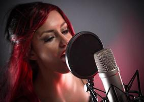 jovem cantora com microfone de estúdio foto