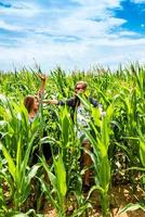 duas meninas se divertindo em um milharal verde foto
