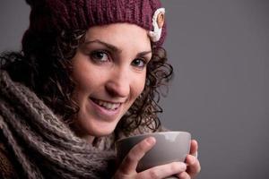 mulher sorridente com uma caneca de uma bebida quente foto