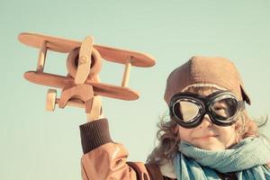 criança feliz brincando com o avião de brinquedo foto