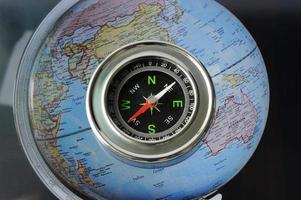 bússola no fundo do mapa mundo foto