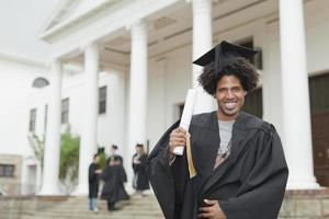 graduado, detentor de seu diploma no campus foto