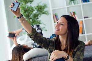 duas mulher jovem e bonita usando telefone celular em casa. foto