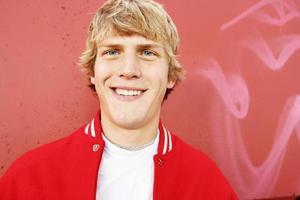 atleta jovem de casaco vermelho letterman foto