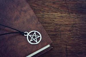 livro e pingente de pentagrama