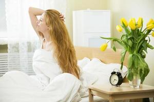 mulher acordando na cama foto