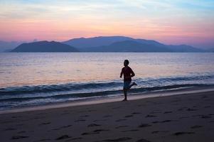 homem correndo na praia foto