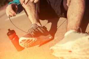 cadarço de gravata desportista em seus tênis de corrida no parque foto