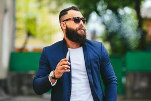 homem de barba fuma cigarro eletrônico