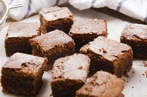 brownie de chocolate em cubos de papel manteiga na mesa de madeira com um foto