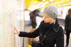 senhora olhando no painel de mapa de transportes públicos.