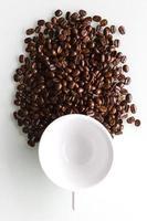 xícara de café branco e grãos de café.