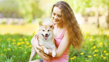 menina feliz e cachorro no parque ensolarado de verão foto