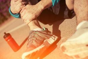 desportista, segurando sua perna foto