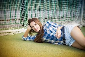 mulher jovem e bonita no campo de futebol foto