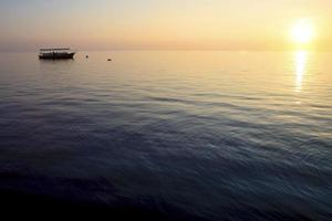 pôr do sol e navio nas Maldivas foto