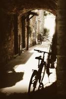 passagem de paralelepípedos antiga com casas de pedra e bicicletas foto