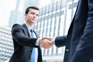 empresários fazendo o aperto de mão na frente de edifícios de escritórios na cidade foto