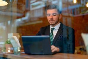 homem de negócios usando o laptop na cafeteria foto