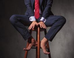 homem de negócios com os pés descalços, sentado em um banquinho foto