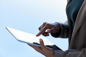 mãos de uma mulher de negócios anônima usando um tablet foto