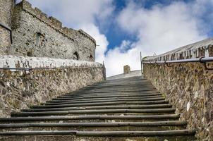 escada de pedra velha e céu nublado foto