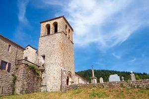 igreja medieval com uma torre sineira e cemitério foto