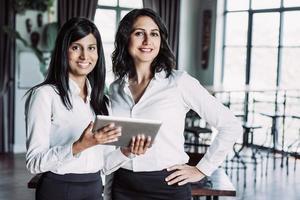 duas colegas alegres usando computador tablet no café