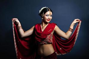 jovem mulher sorridente em roupas tradicionais indianas dançando