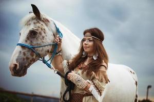 menina indiana com cavalo branco no fundo do céu foto