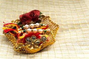 fio rakhi em suporte de ouro com tika e arroz foto