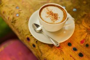 cappuccino quente em um pires com fundo colorido foto
