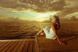 mulher caucasiana descansa no cais de madeira para o Oceano Índico foto