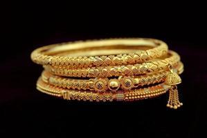 quatro pulseiras de ouro ornamentadas em um fundo preto foto